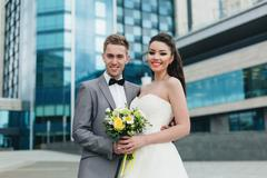Newlyweds smiling in front of the building Stock Photos