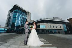 Newlyweds in front of the high blue building Stock Photos