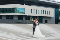 Newlyweds embracing in fron of the building Stock Photos