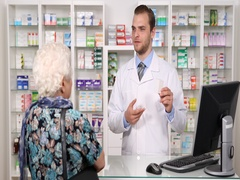 Experienced Pharmacist Man Talking with Old Woman About Pills Pharmaceutics Shop Stock Footage