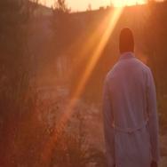 Thoughtful man walking towards sunset/sunrise. Stock Footage