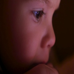 A little boy watches cartoons in the tablet late in the evening closeup face Stock Footage