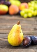 Bio pear and plums with other fruits in background Stock Photos