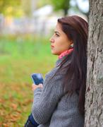 Beautiful girl messaging with phone in autumn park Stock Photos