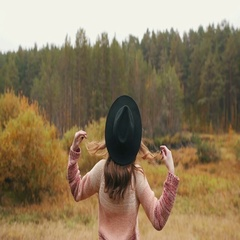The back of a girl with long hair in a hat. Bright girl in the forest. Stock Footage