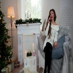 Woman talking on a mobile phone New Year holidays in a cozy atmosphere, while Stock Footage