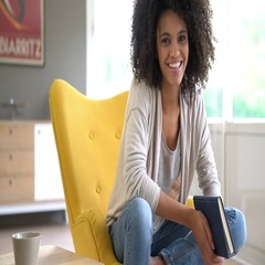 Attractive mixed race woman sitting in yellow armchair Stock Footage