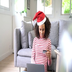 Mixed race woman in Christmas outfit receiving e-order Stock Footage