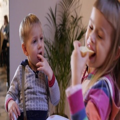 Happy cute little children in a restaurant funny eating a food and smile play Stock Footage