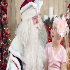 Beautiful little girl having fun smiling Santa Claus and sitting on his lap. Stock Footage