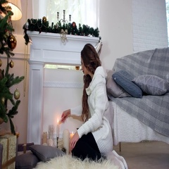 Winter, girl lights a candle sitting by the fireplace near the Christmas tree Stock Footage