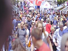 Many people walking through town fair street long shot 4K Stock Footage