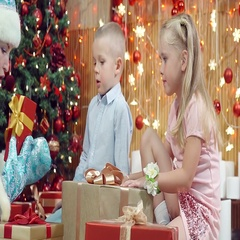 The boy and the girl choose Christmas gifts and assistant of Santa Claus. Stock Footage