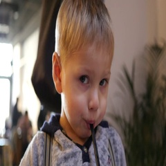 Cute little child boy funny drinking fresh apple juice from a straw Stock Footage