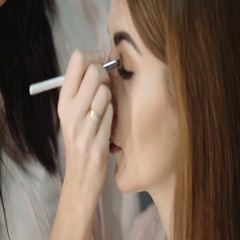 Professional makeup artist putting cosmetics. Focus on the model's face Stock Footage