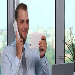 Happy Business Man Talk Landline Phone Positive Answer and Using Tablet Office Stock Footage