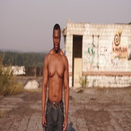 Strong angry black bare-chested man standingon the roof of an abandoned building Stock Footage