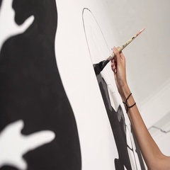 Girl's arm drawing on wall with black paint Slow motion Stock Footage