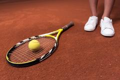 Tennis racket and ball lying on the surface of court Stock Photos