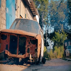 Abandoned rusty red car in the yard in the summer Stock Footage