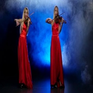 Two girls blonde to play the fiddle. Smoky background with backlight. Slow Stock Footage