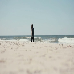 A dark-haired pregnant woman is having a peaceful walk along the sea shore on a Stock Footage