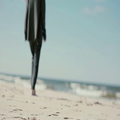 A woman with long dark hair is walking barefoot on a sandy beach towards the Stock Footage