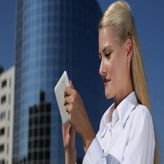 Businesswoman Browsing Digital Tablet Receiving Good News Front of Tall Tower Stock Footage