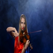 Woman in a red dress playing the fiddle. Studio. Smoke Stock Footage
