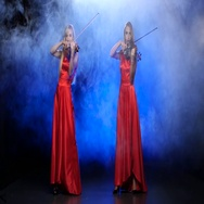 Two girls in a red dress playing the violin. Studio. Smoke Stock Footage