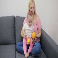 Mother with baby playing on couch Stock Footage