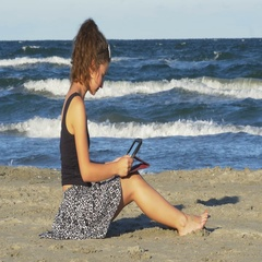 Beautiful young woman sitting on the beach and tipping on her tablet pc on a sum Stock Footage