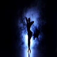 Graceful girl dancing in studio, silhouette. Dark background, blue backlight Stock Footage