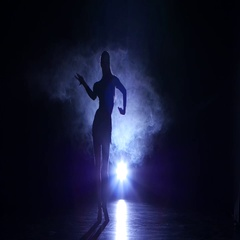 Girl dancing movements of salsa, rumba, silhouette. Dark background, blue Stock Footage
