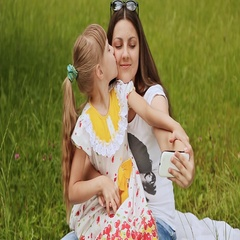Girl kissing her sister, and they do selfie on grass Stock Footage