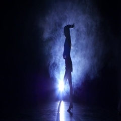 Woman dancing in studio, silhouette. Dark background, blue backlight Stock Footage