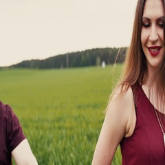 Young woman in love holding her partner by the hand walking in a field. The man Stock Footage