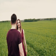Romantic young couple. They hug and spin around in a green field. Slow mo Stock Footage