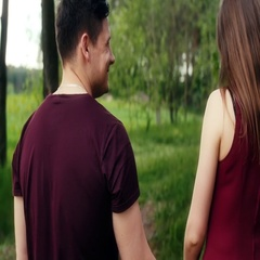 Back view of romantic young couple in love walking in forest, holding hands Stock Footage