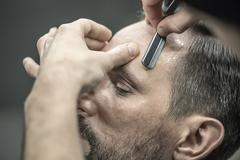 Trimming hair in barbershop Stock Photos