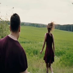 Couple in love laugh, having fun in a field. Man chases his woman like a child Stock Footage