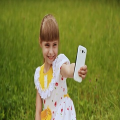 Little girl in a white dress makes selfi on the meadow Stock Footage