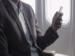 Detail of African American airline passenger's hand using cellphone 4K Stock Footage