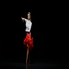 Girl dancing cha-cha-cha in a studio on a dark background Stock Footage