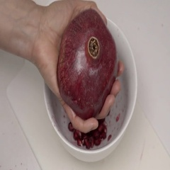Banging the back of a Pomegranate to release the seeds.  4K UHD. Stock Footage