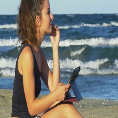 Beautiful young woman in romantic mood holding a tablet pc by the sea Stock Footage