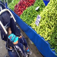 Vegetable counter and child sleeping in pushchair Stock Footage