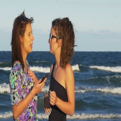 Girl talking with her best friend and looking at the smart phone on the beach Stock Footage