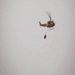 Yellow firefighting helicopter with red bucket Stock Footage