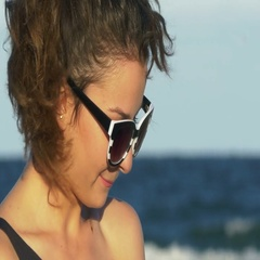 Face closeup of a young woman laughing hard by the sea Stock Footage